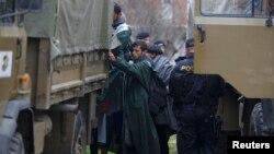 Policia e Maqedonisë duke i vendosur migrantët nëpër kamionë, pasi ata e kanë kaluar kufirin nga Greqia