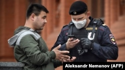 A man shows his digital ID to a Russian police officer amid a coronavirus lockdown on May 6.
