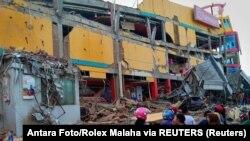 Люди стоят перед поврежденным торговым центром после землетрясения в Палу, остров Сулавеси, 29 сентября 2018 года