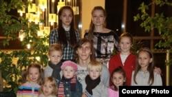 Екатерина Онохова (сверху справа) вместе с мужем Александром (в центре) и двумя собственными и семью приемными детьми. 2010 год.