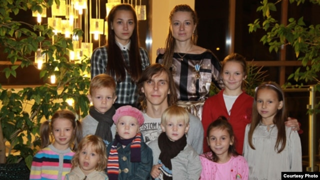 This photo from 2010 shows Katsyaryna Onakhava (top right) and her husband Alyaksandr (middle), along with two biological and seven adopted or foster children.