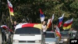 Оңтүстік Осетия туын ұстаған аймақ тұрғындары (Көрнекі сурет).