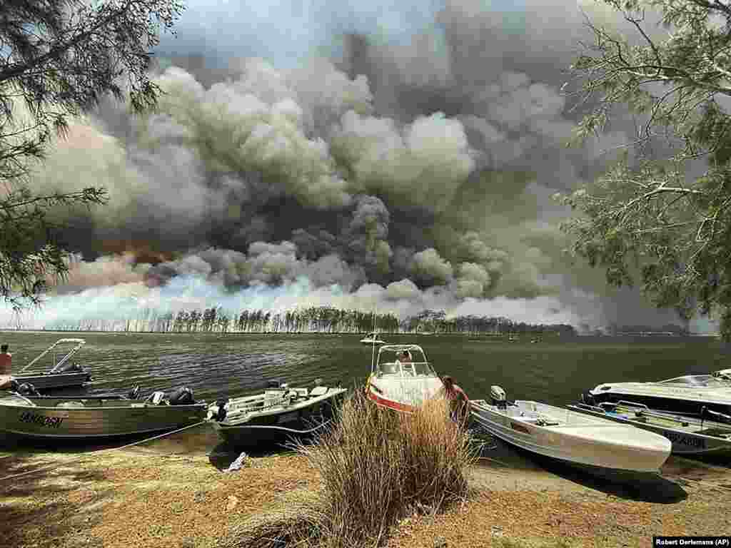 Boats are pulled ashore as smoke and wildfires rage behind Lake Conjola, Australia. Thousands of tourists fled Australia's wildfire-ravaged eastern coast ahead of worsening conditions as the military started to evacuate people trapped on the shore further south. The fires have killed at least 24 people and destroyed more than 1,200 homes. (AP/Robert Oerlemans)