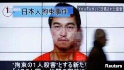 Жапон журналисі Кендзи Гото көрсетілген үлкен экранның қасынан өтіп жара жатқан адам. Токио, 25 қаңтар 2015 жыл.