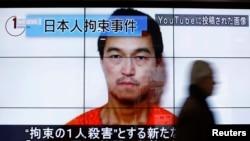 Мужчина проходит мимо экрана с изображением японского журналиста Кэндзи Гото. Токио, 25 января 2015 года.