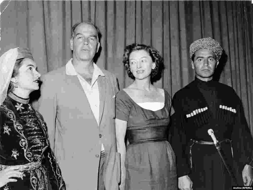 Radio Liberty employees relax in national dress at a retreat in Bavaria in the late 1950s. From left, Aza Ryzer, the head of the music library; Radio Liberty President Howland H. Sargeant; film star Myrna Loy, who was married to Sargeant; and Ibrahim Gelischanow, a founding member of the North Caucasus Desk.