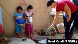 ينتظرون دورهم للحصول على ماء الشرب الشحيح (من الارشيف)
