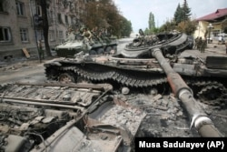 Цхінвалі, расейскія вайскоўцы праяжджаюць каля падбітага грузінскага танка, жнівень 2008