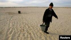 Местный житель несет ведро с водой из колодца посреди пустыни на месте Аральского моря в Казахстане.