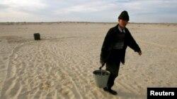 Арал теңізі маңындағы қазақ ауылының тұрғыны құдықтан су тасып жүр. 21 сәуір 2005 жыл.