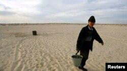 Житель села Каратерен Кызылординской области несет воду. 16 апреля 2005 года.