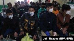 Группа людей, ожидающих проверки в пункте пропуска на границе Афганистана с Ираном.