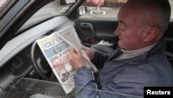 Газет оқып отырған таксист. Киев, 29 қазан 2012 жыл