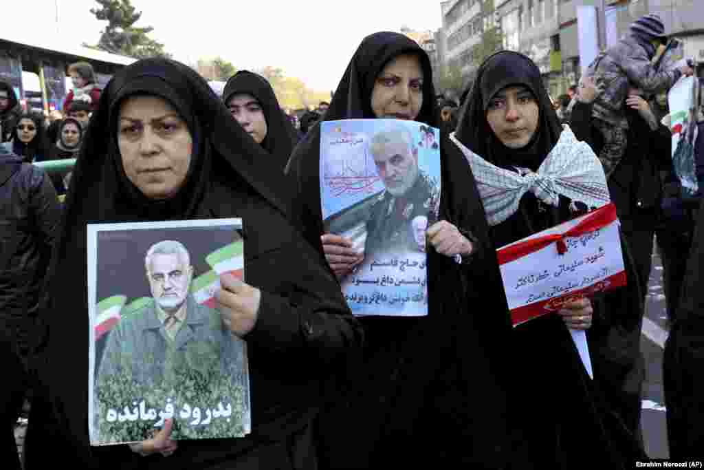 Mourners holding posters of Iranian General Qasem Soleimani.
