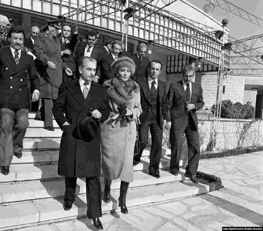 محمدرضا شاه پهلوی و همسرش شهبانو فرح پهلوی در هنگام خروج از پاویون فرودگاه مهرآباد در ۲۶ دی ماه ۵۷