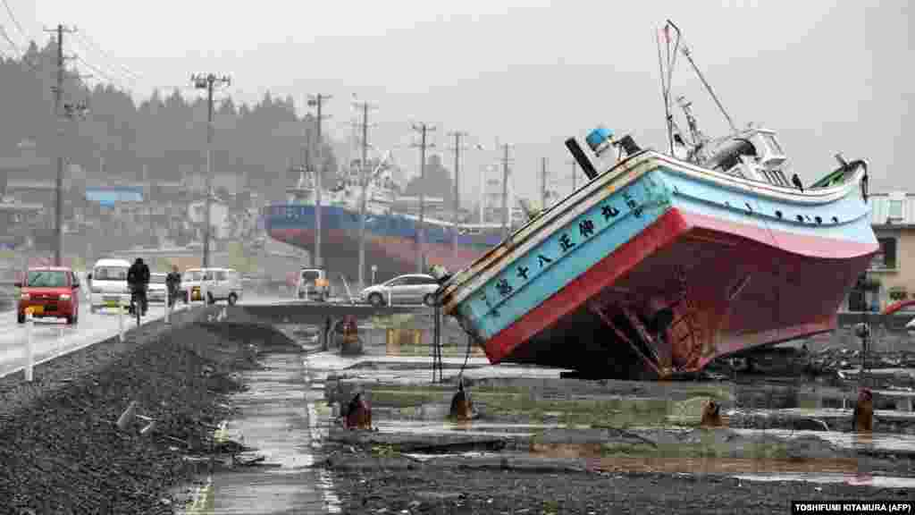 Vehicles move among fishing vessels that were carried from Kesennuma port by the March 11, 2011, tsunami, in the city of Kesennuma, Japan. (AFP/Toshifumi Kitamura)