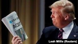Presidenti amerikan, Donald Trump duke mbajtur me krenari gazetën që tregon për shfajësimin e tij.