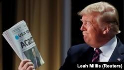 Президент США Дональд Трамп тримає газету USA Today, у якій надруковані результати слухань щодо імпічменту
