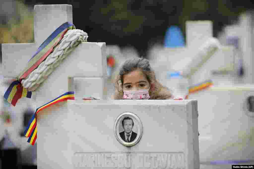 Ребенок в защитной маске стоит возле памятника жертвы антикоммунистической революции 1989 года во время поминальной религиозной службы в Бухаресте по погибшим во время восстания. (AP/Вадим Гирда)