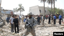 Америкалык аскер Ирактын Кут шаарындагы бомба жарылган жерде баратат. 25-август 2010