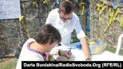 Святослав Фояк допомагає відвідувачу українського фестивалю в Торонто написати на стрічці привітання українському бійцеві, 20 серпня 2016 року