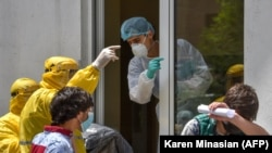Armenia -- A hospital worker (C) wearing a protective face mask and outfit, speaks with two ambulance doctors wearing yellow protective suits at the Grigor Lusavorich Medical Center in Yerevan, May 27, 2020