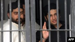 Shahrukh Jatoi (right) gestures while his accomplice Siraj Talpur looks on from a court lockup before being convicted for murder in the Pakistani port city of Karachi on June 7.