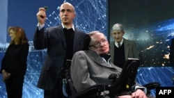 "Yury Milner holds up a ""Starchip"" in the presence of renowned cosmologist Stephen Hawking in New York on April 12"