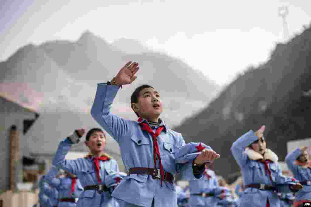 Children dressed in uniform sing after raising the national flag at the Beichuan Red army elementary school in Beichuan, southwest Sichuan Province, China. (AFP/Fred Dufour)