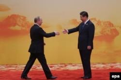 Қытай президенті Си Цзиньпин (оң жақта) Ресей президенті Владимир Путинді қарсы алып тұр. Пекин, 10 қараша 2014 жыл.