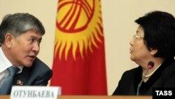 Мурдагы президент Роза Отунбаева жана азыркы президент, Убактылуу өкмөттүн учурунда премьер-министрлик кызматты аркалаган Алмазбек Атамбаев өкмөттүн Бишкектеги жыйынында, 20-декабрь, 2010-жыл.