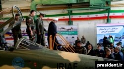 A handout picture released by the Iranian Presidency on August 21, 2018, shows President Hassan Rouhani (C) visiting the National Defence Industry exhibition in the capital Tehran. He inspected what Iran says is its homegrown fighter jet.