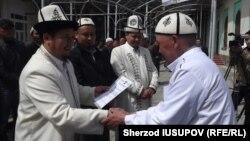 Muftiy o'rinbosari Ravshan Eratov da'vatchi sertifikatini taqdim etmoqda.