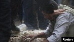 أب سوري يحاول البحث عن بناته في أنقاض مبنى إنهار في قصف قرب دمشق