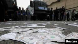 Turkish riot police secure an area as fake U.S.dollar notes with the image of Prime Minister Recep Tayyip Erdogan are seen spread across a road leading to a building belonging to the ruling AK Party during a protest against Erdogan and his government in Ankara. (Reuters/Umit Bektas)