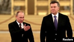 Russian President Vladimir Putin (left) gestures to guide Ukrainian President Viktor Yanukovych toward a meeting of the Russian-Ukrainian Interstate Commission at the Kremlin in Moscow in December.