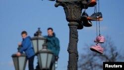 Шеруге келген мәскеуліктер көшедегі шамдарға шығып тұр. Бергі шамда наразылық шерулерінің символына айналған кроссовкалар ілінген. Мәскеу, 26 наурыз 2017 жыл.