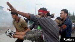 Сторонники Мухаммеда Мурси несут раненого участника акций протеста в Насре, 27 июля 2013 года.