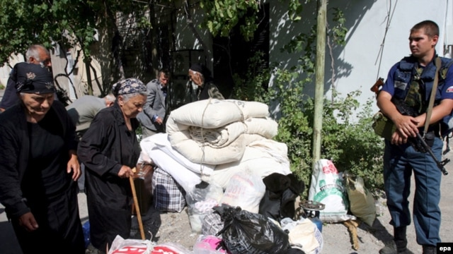 Georgians with their belongings wait to be evacuated by the Russian Emergency Situations Ministry from the village of Kurta, near Tskhinvali, South Ossetia, in August 2008.