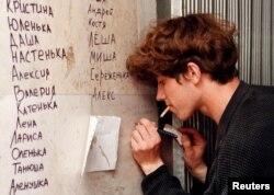 Малады чалавек піша імёны ахвяраў цісканіны на Нямізе, 1 чэрвеня 1999 году