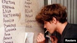 Хлопец піша імя ахвяры цісканіны на месцы трагедыі. 1 чэрвеня 1999 года