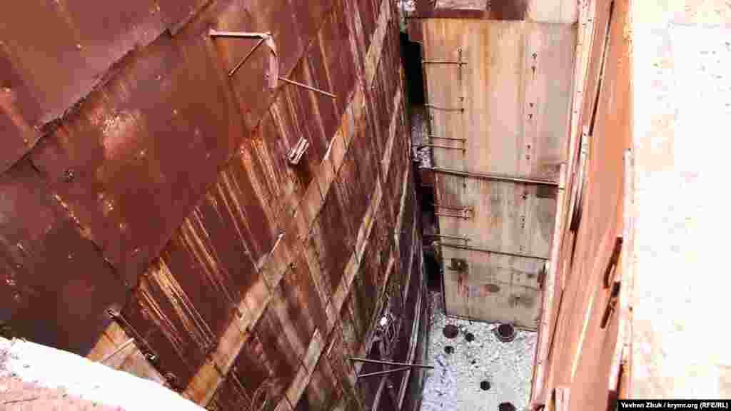 Сегодня Крымскую АЭСпродолжают разбирать на стройматериалы, экскаватор гидравлическим молотом разбивает многоэтажное техническое здание, находящееся рядом с реакторным блоком АЭС