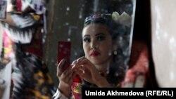 Сахнаға шығуға дайындалып отырған өзбек ұлттық киімін киген қыз. Ташкент, 16 мамыр 2015 жыл. (Көрнекі сурет)