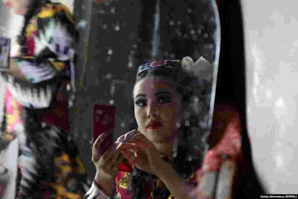 Танцовщица за кулисами готовится к исполнению узбекского танца.
