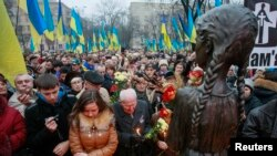 Ukraine -- People attend a commemoration ceremony at a monument for Holodomor victims in Kyiv, November 23, 2013