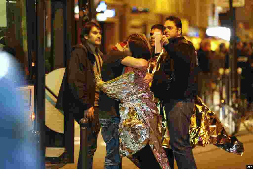 Арнайы топ жасағы терроршылар басып алған «Батаклан» өнер орталығын босатқаннан кейін ғимарат сыртында бір-бірін құшақтап тұрған адамдар. 14 қараша 2015 жыл.