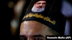 LEBANOn -- A Lebanese Shiite supporter of the Iranian-backed Hizballah group, with a portrait on his head of Hizballah leader Sayyed Hassan Nasrallah, attends an activities to mark the ninth of Ashura, a 10-day ritual commemorating the death of Imam Husse