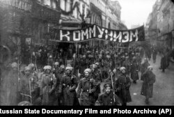 "Armed soldiers carrying a banner reading ""Communism"" march along Nikolskaya Street toward the Kremlin in Moscow in 1917."