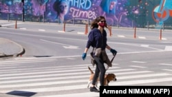 Девушка с собакой переходит дорогу в Приштине, Косово. Апрель 2020 года.