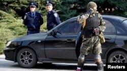 Мужчина в военной форме и в бронежилете стоит рядом со зданием Донецкой областной администрации. 22 апреля 2014 года.